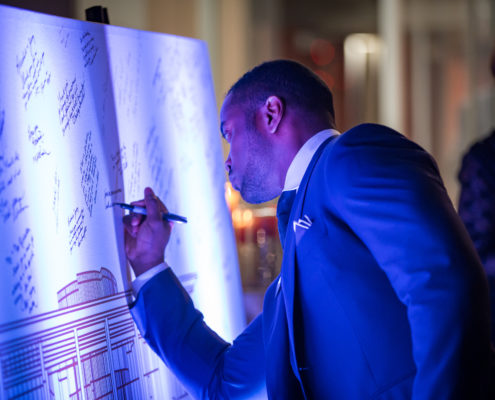 To commemorate the grand opening of an art building, guests signed a giant blueprint of the building as the departed.