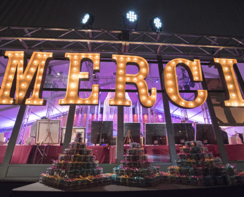 """As guests departed for the evening, they were thanked with chocolate and raspberry flavored macarons and giant marquee letters spelling out """"Merci""""."""