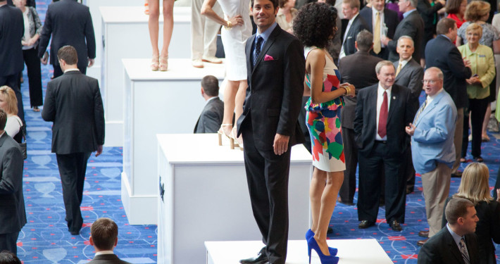 Models showcasing the new spring line atop of large pedestals during a networking reception were a unique sponsor benefit for this fashion retailer at a corporate event.