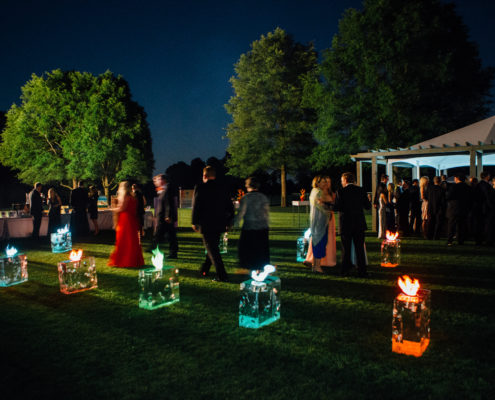 At a fire and ice themed fundraiser, ice blocks lined along a pathway led guests inside a tent. When guests departed, the ice blocks transformed into fire adding a surprise element.